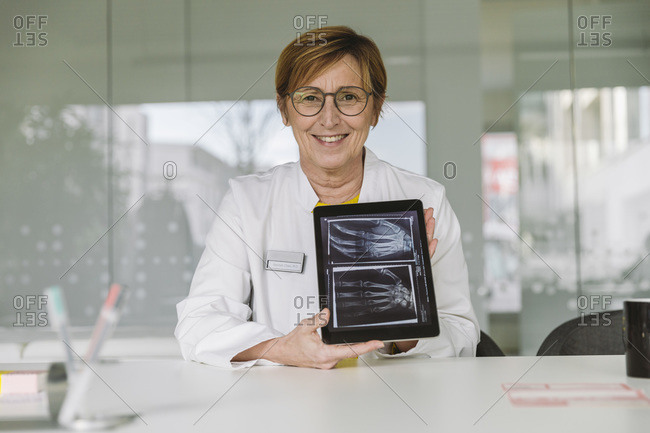 Doctor sitting at desk showing  x-ray image of hand on digital tablet