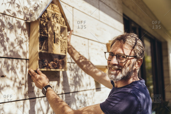 Portrait of man attaching insect hotel