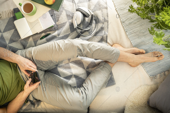Overhead view of man lying on sofa holding smartphone