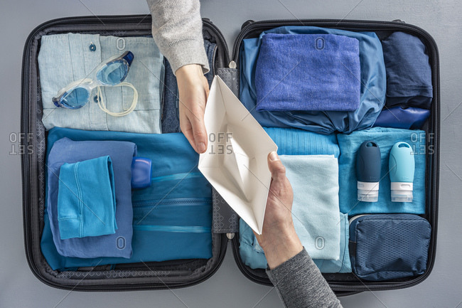 Overhead view of woman handing over paper boat to man over packed suitcase
