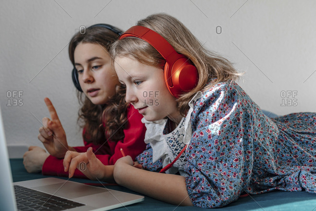 Two sisters with headphones lying together on bed looking at laptop