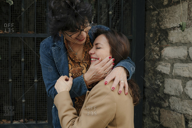 Senior woman stroking cheek of her happy adult daughter