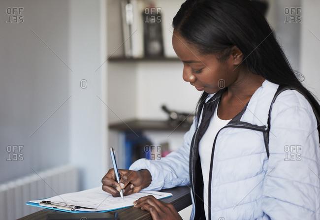 Patient filling in form at reception desk of a dental practice
