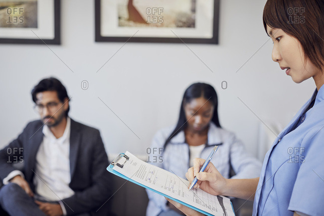 Receptionist checking form in waiting room of a dental practice