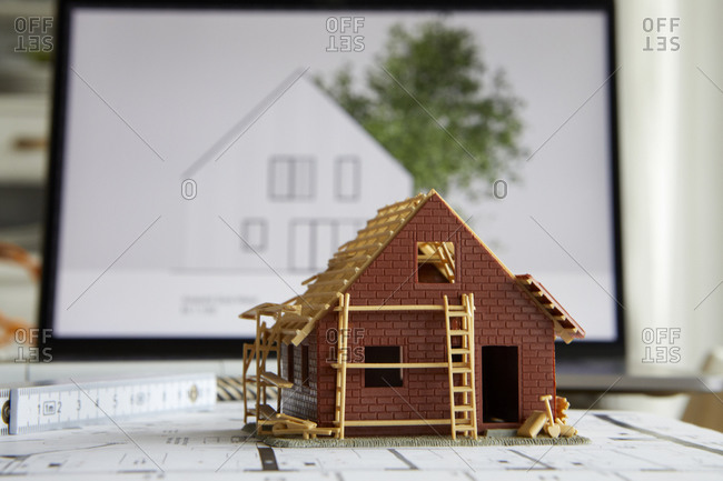 Architecture- model of home ownership on construction plan- laptop in the background