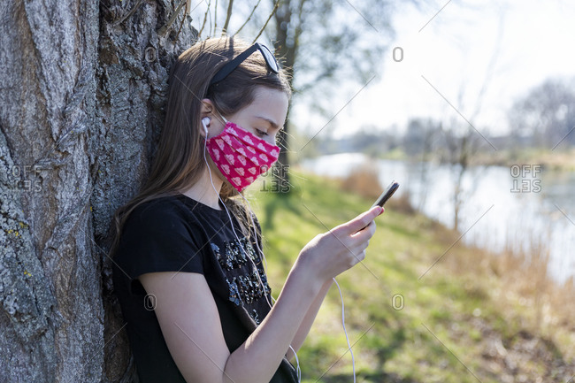 Girl with homemade protective mask using smartphone and leaning on tree