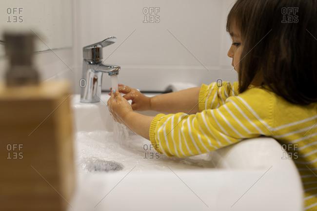 Little girl washing her hands