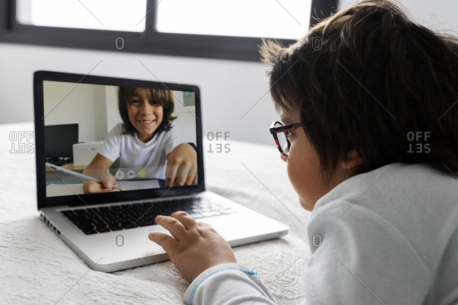 Little boy lying on bed using laptop for video chat