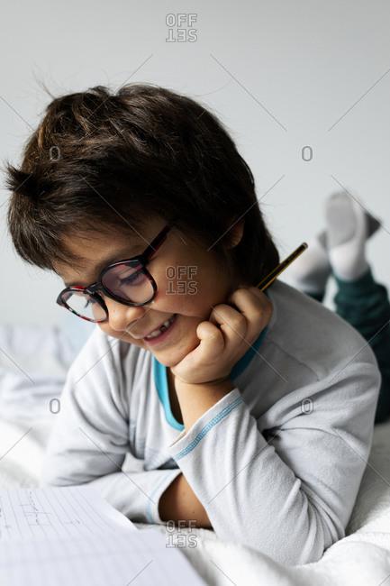 Portrait of little boy lying on bed doing homework
