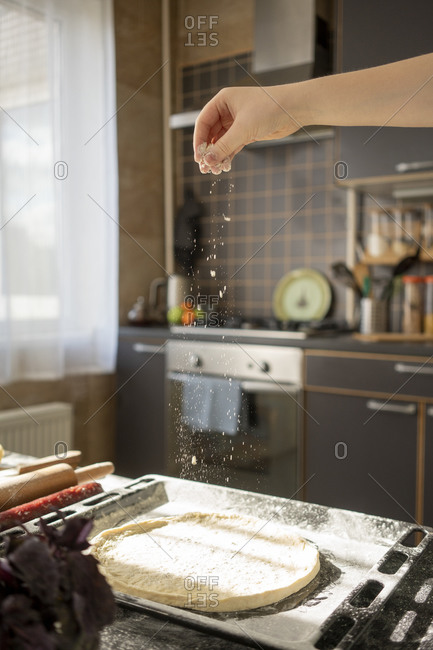 Boy's hand scattering flour on pizza base