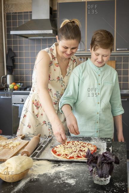 Mother and son scattering grated cheese on pizza base