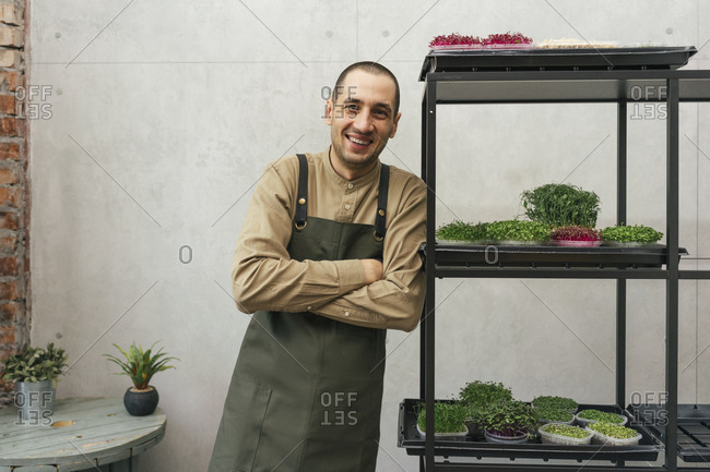 Portrait of happy man leaning against shelf with microgreens