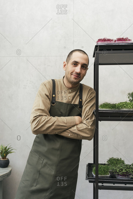 Portrait of smiling man leaning against shelf with microgreens