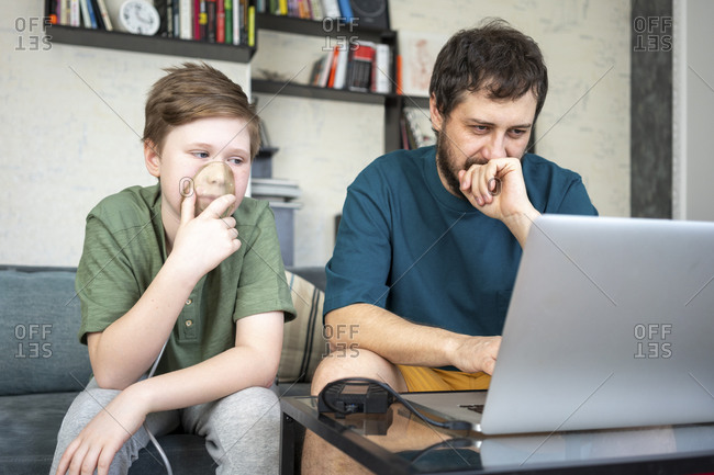 Portrait of father and son sitting together on the couch using laptop