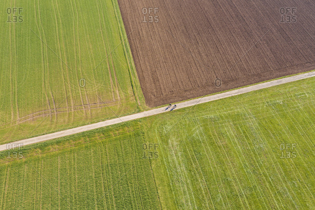 Germany- Baden-Wurttemberg- Remshalden- Aerial view of two cyclists riding along countryside dirt road in spring