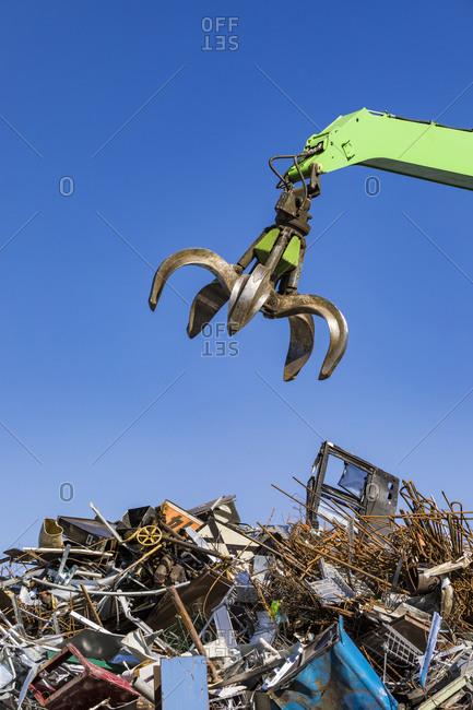 Germany- Baden-Wurttemberg- Stuttgart- Mechanical claw over heap of scrap metal lying in junkyard