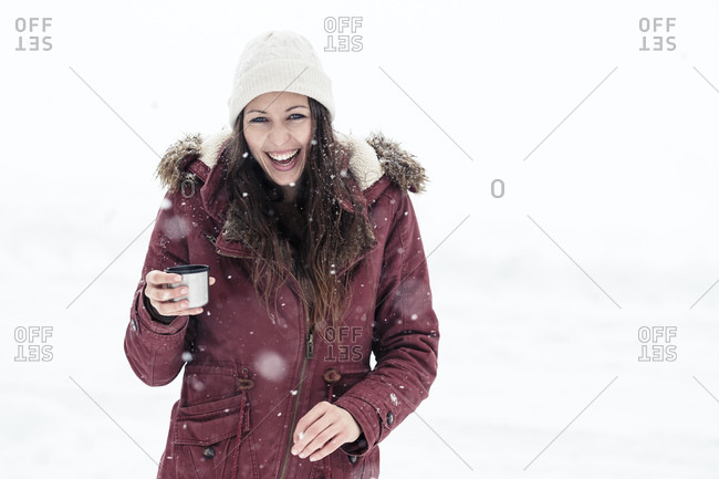 Portrait of laughing young woman with hot beverage in snow