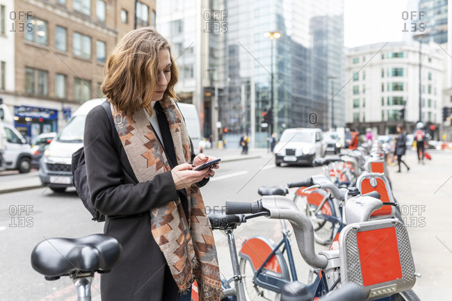 Woman with smartphone in the city using rental bike- London- UK