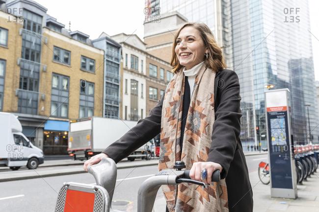 Happy woman in the city using rental bike- London- UK