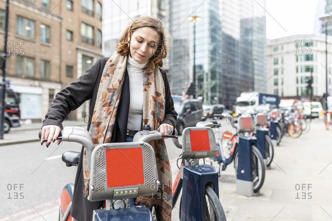 Woman in the city using rental bike- London- UK