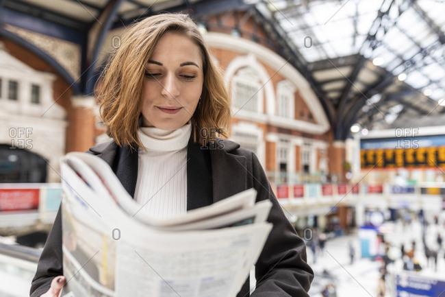 Woman at train station reading a newspaper- London- UK