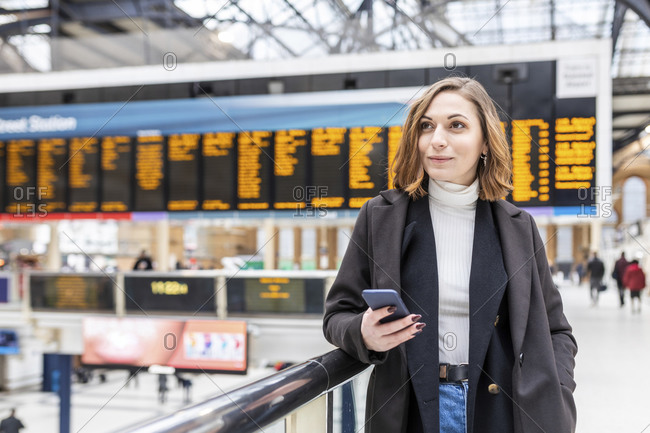 Woman at train station holding a mobile phone- London- UK