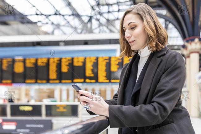 Woman at train station using mobile phone- London- UK
