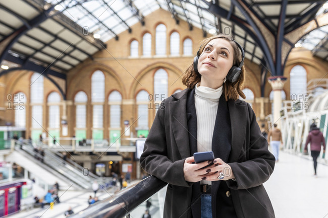 Woman at train station with headphones and mobile phone- London- UK