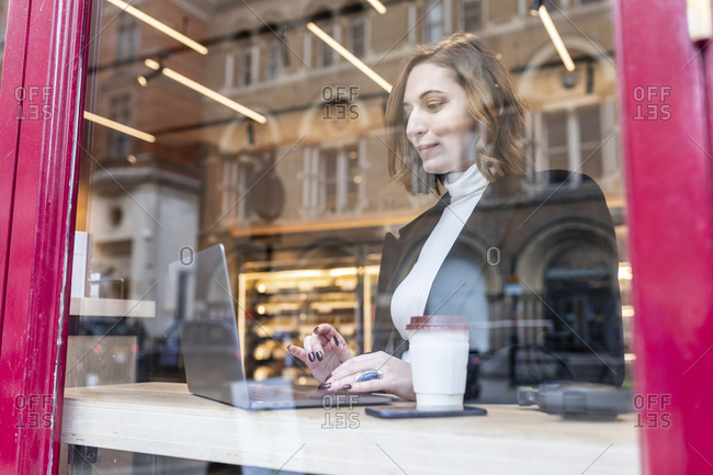 Businesswoman using laptop at a cafe in the city