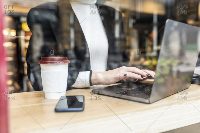 Close-up of businesswoman using laptop at a cafe in the city