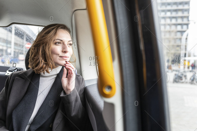 Woman in the rear of a taxi looking out of the window- London- UK