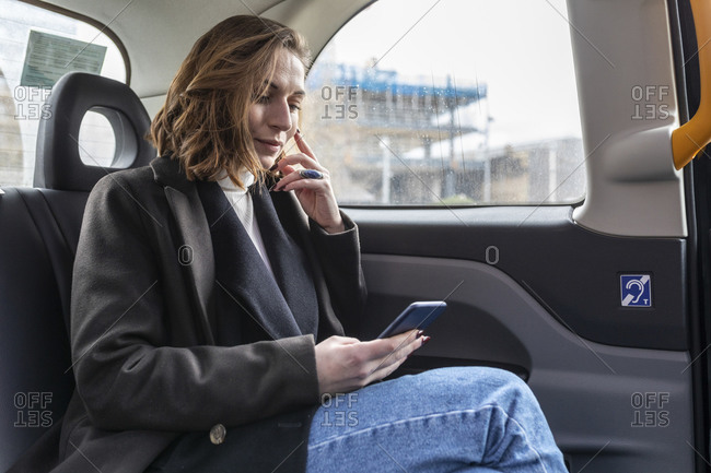 Businesswoman in the rear of a taxi looking at the phone