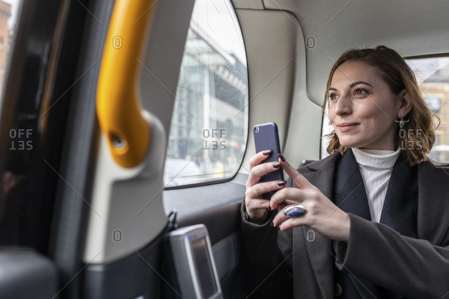 Businesswoman in the rear of a taxi looking out of the window- London- UK