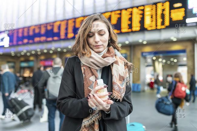 Woman using sanitizing hand gel at train station