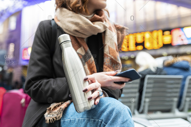 Woman sitting at train station with thermos flask and mobile phone