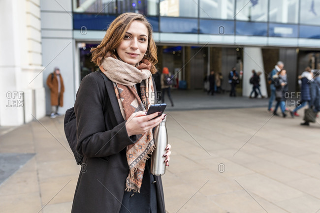 Portrait of woman with mobile phone in front of train station- London- UK