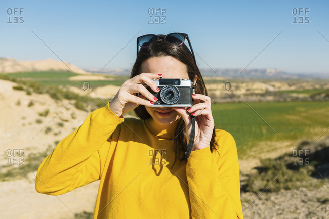 Woman taking pictures with a vintage camera- Bardenas Reales- Arguedas- Navarra- Spain