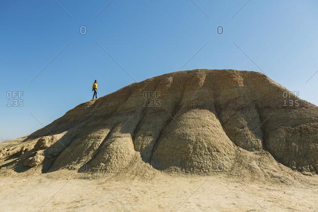 Woman walking on a hill in desertic landscape of Bardenas Reales- Arguedas- Navarra- Spain