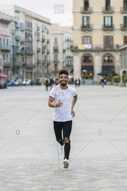 Portrait of laughing young man running on a square- Barcelona- Spain