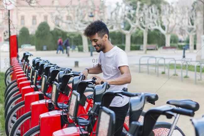 Young man taking a rental bike- Barcelona- Spain