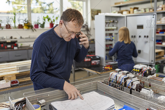 Man on the phone checking circuit diagram in electrical workshop