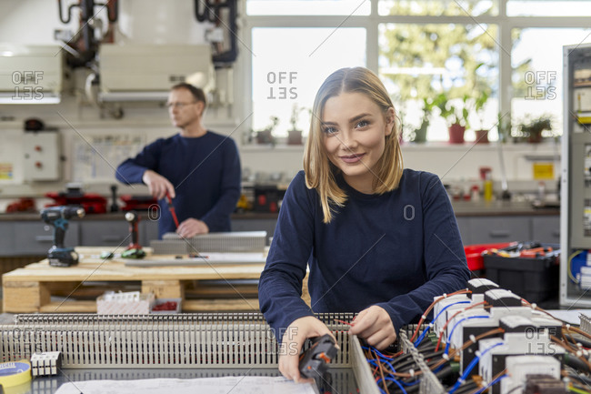 Portrait of smiling female electrician working on circuitry in workshop