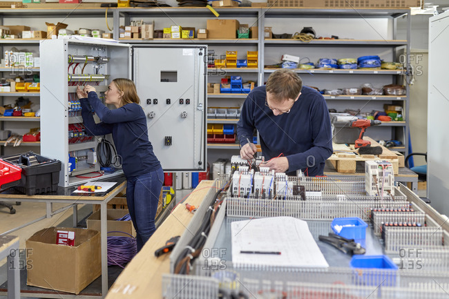 Two electricians working in workshop