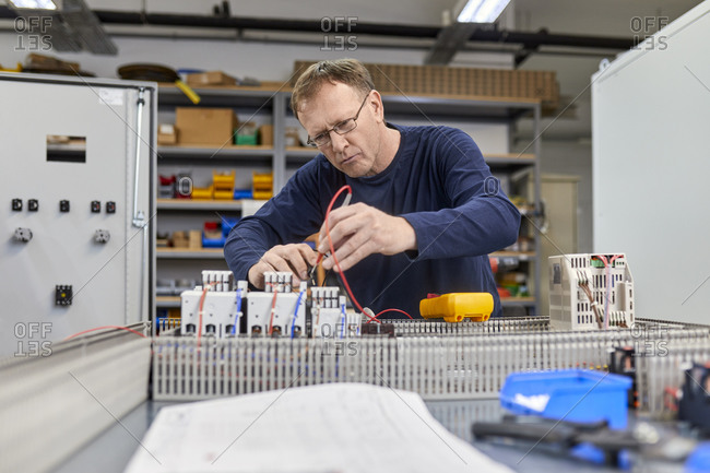 Electrician working on circuitry in workshop