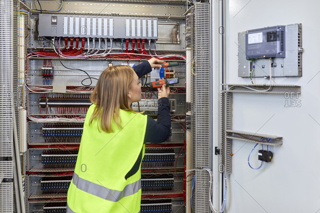 Female electrician working with voltmeter at fuse box