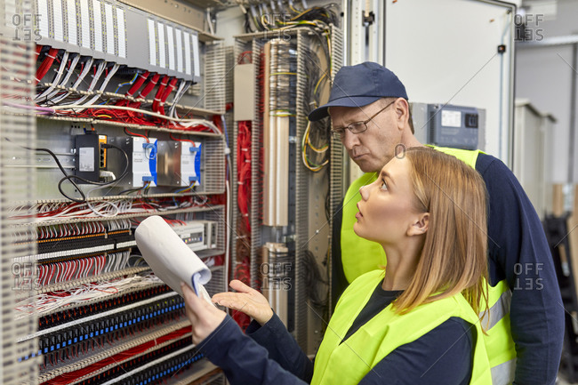 Two electricians with plan looking at fuse box