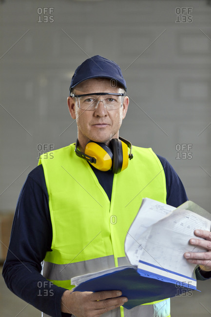 Portrait of worker in protective workwear holding folder