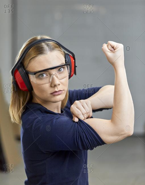 Portrait of female worker flexing her muscles