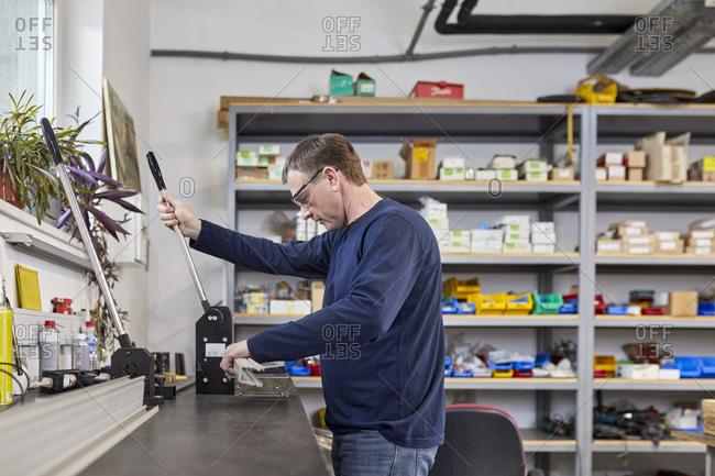 Man using punching machine in workshop