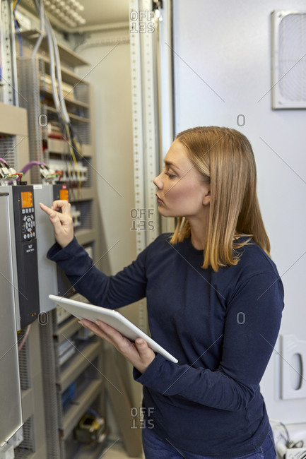 Female electrician with tablet adjusting circuitry at junction box